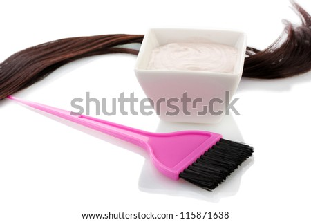 Bowl with hair dye and pink brush on white background close-up