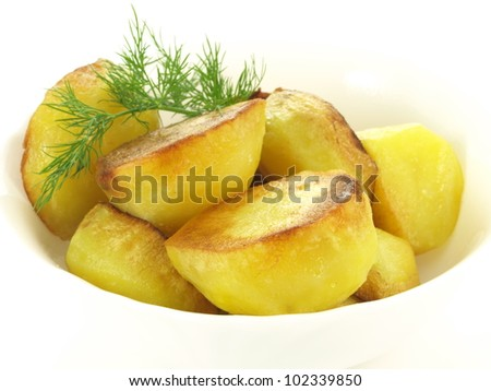 Bowl with halves of grilled crusty potatoes