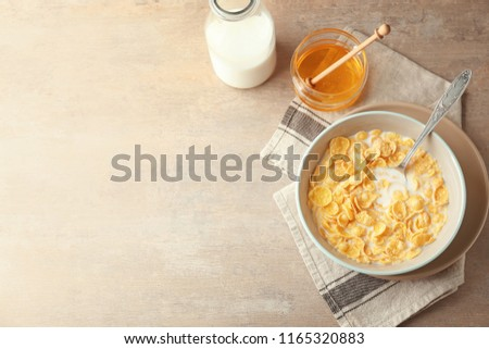 Bowl with healthy cornflakes, milk and honey on light table #1165320883