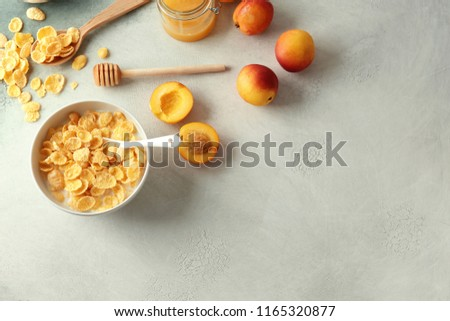 Bowl with healthy cornflakes, milk, honey and peaches on light table #1165320877