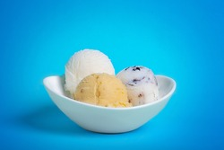Bowl with ice cream balls with blue bacground.