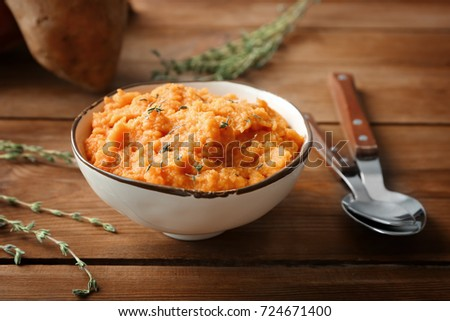 Bowl with mashed sweet potato on wooden background #724671400
