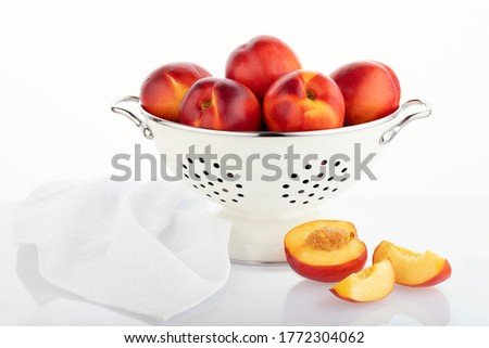 Bowl with nectarines on a white background. Fresh juicy nectarines in a white colander and halves of nectarines with reflection.