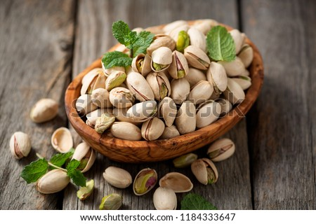 Bowl with pistachios on a wooden table.