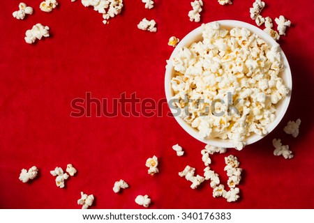 bowl with popcorn on red background. mock up. top view.
