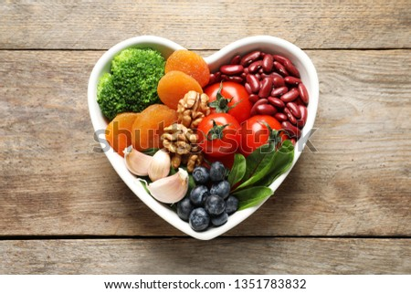 Bowl with products for heart-healthy diet on wooden background, top view