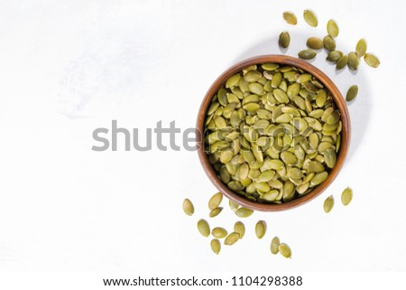 bowl with pumpkin seeds on white background, top view horizontal #1104298388