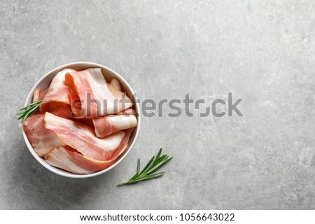Bowl with raw bacon rashers on grey background