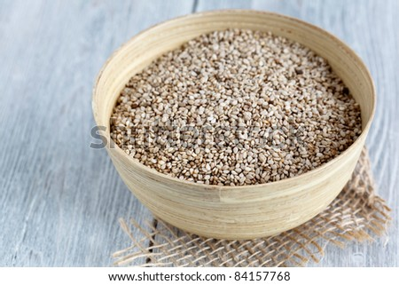 Bowl with sesame on white wooden surface.