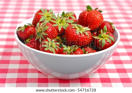 Bowl with strawberries on a chequered patterned table-cover