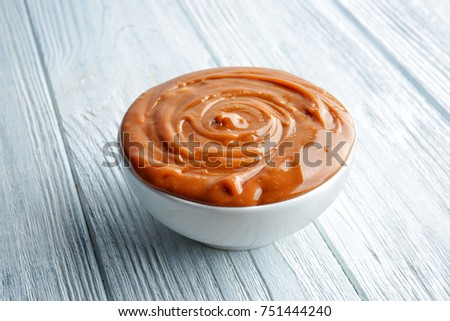 Bowl with tasty caramel sauce on wooden table