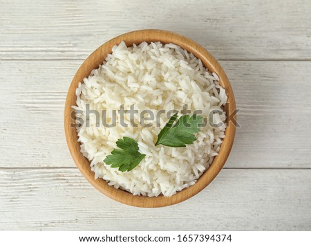 Bowl with tasty cooked rice and parsley on white wooden table, top view
