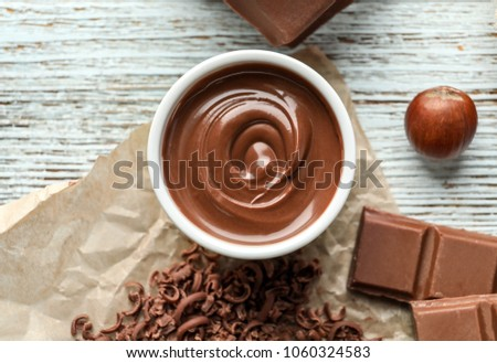 Bowl with tasty melted chocolate on wooden background