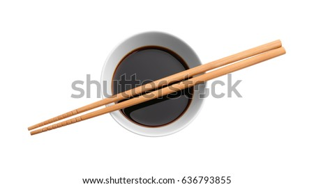 Bowl with tasty soy sauce and chopsticks on white background #636793855
