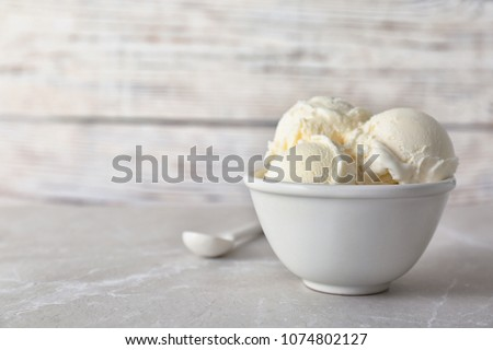Bowl with tasty vanilla ice cream on table against light background #1074802127