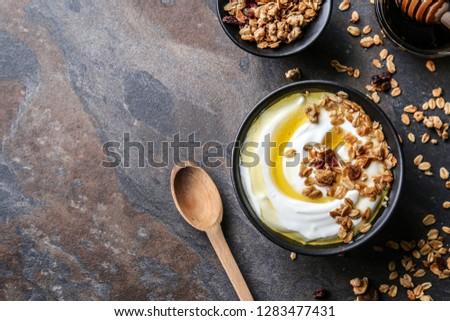 Bowl with tasty yogurt, honey and oatmeal on dark background