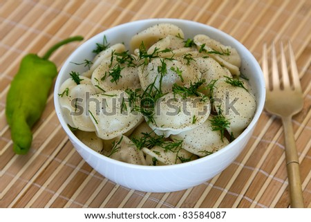 Bowl with traditional Russian dish - pelmeni.