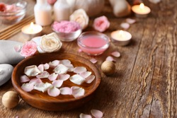 Bowl with water and rose petals on wooden table