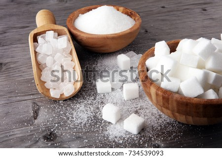 Bowl with white sand, crystal and lump sugar on wooden background.