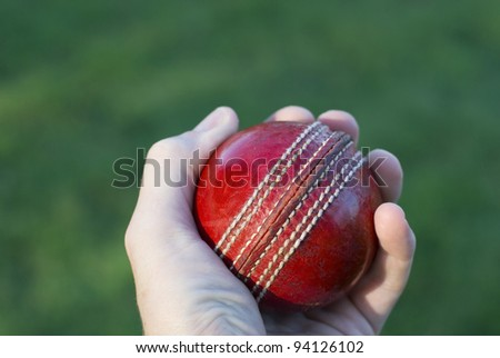 Bowler's hand holding a red cricket ball over green grass.