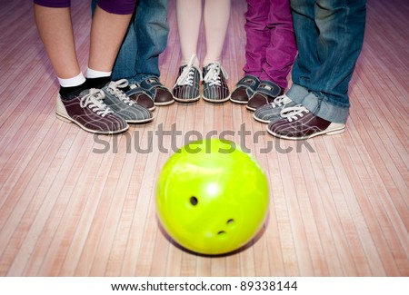 bowling ball and children's feet in shoes for bowling