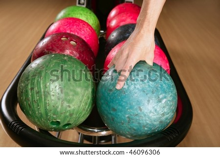 Bowling ball in player man hand in colorful rows