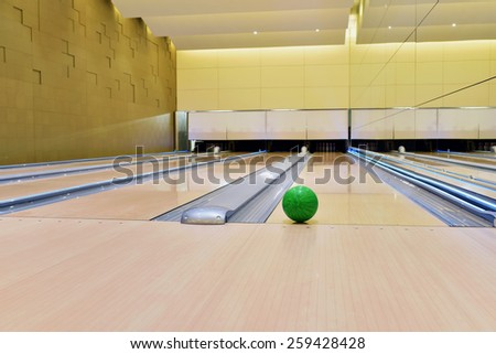 Bowling ball lying on bowling alley\ It will be strike. Green bowling ball rolling along bowling alley
