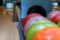 Bowling balls lie in a holder in a line. Colored balls and bowling lane.