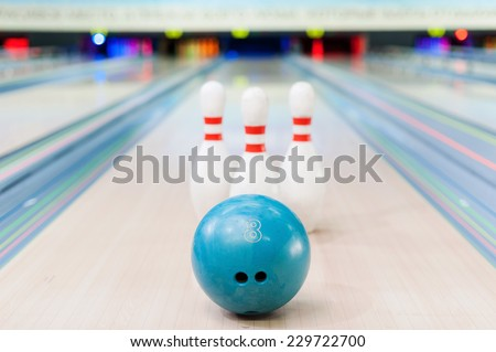 Bowling game. Close-up of blue bowling ball lying against pins staying on bowling alley