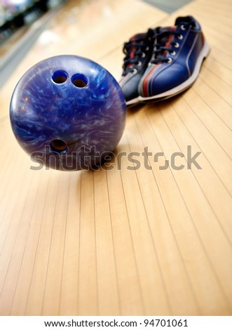 Bowling kit with shoes and ball on the alley