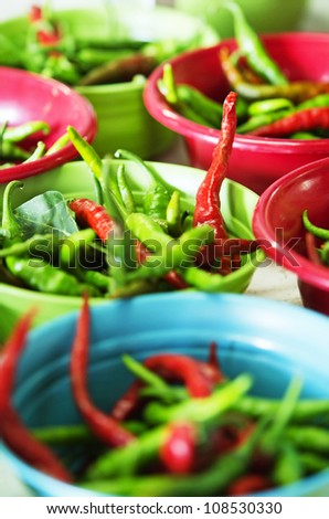 Bowls of fresh hot Cayanne peppers in an open-air farmers market.