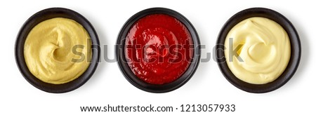 Bowls of ketchup mayonnaise and mustard isolated on white background, top view