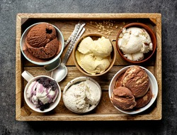 bowls of various ice creams on dark gray table, top view
