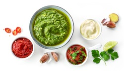 bowls of various sauces isolated on white background, top view