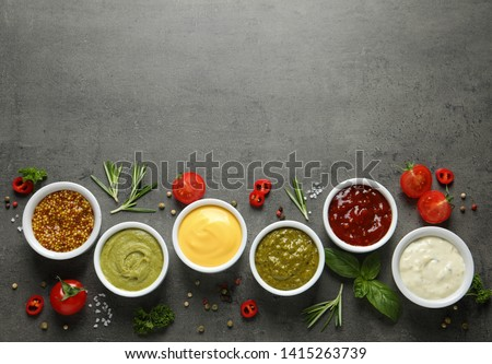 Bowls with different sauces and ingredients on gray background, flat lay. Space for text Stock photo ©