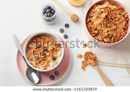 Bowls with healthy cornflakes, milk and blueberry on white table #1165320859