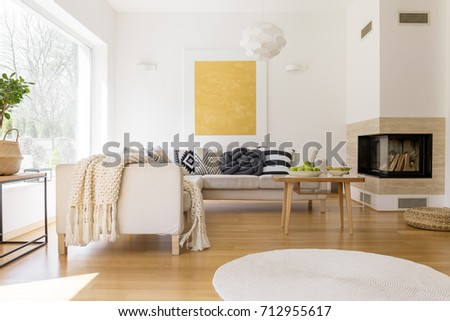 Bowls with pears and apples on small coffee table near beige couch set with black and white pillows #712955617