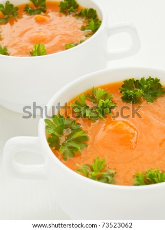 Bowls with pumpkin soup and parsley. Shallow dof.