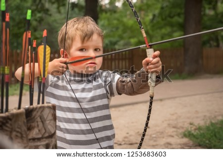 Bowman background. Boy with bow and arrow concentrated on target. Kid stared at target. Child directed arrow at a target. Children and sports. Physical training. Alternative schooling.