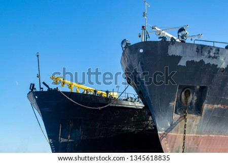 Bows of cargo vessels in port against sky #1345618835