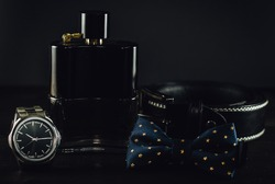 Bowtie, perfume bottle, leather belt and silver wristwatch on the dark wooden table. Close up, black background, male accessories.