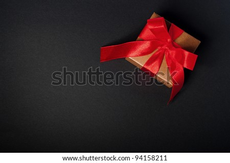Box, bow and ribbon on dark background