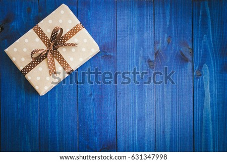 Box in craft paper, eco paper on the wooden table. Top view. Brown paper wrapped gift box with satin ribbon bow on a old rustic blue wood background. For your design. Retro filter. Copy space for text