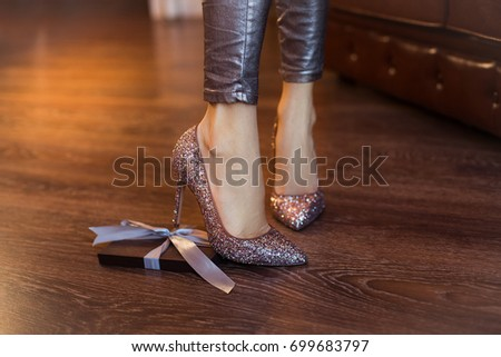 Box in special gift. Beautiful legs and high-heeled shoes. Box with present laying on the floor #699683797