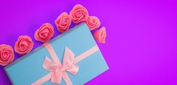 Box is container with flat base and sides, rectangular shaped, having lid, colored tape, made to look attractive and designed to be given as gift. It is decorated with pink flowers.