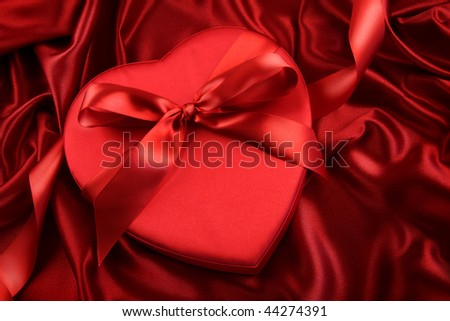 Box of chocolate on red satin background