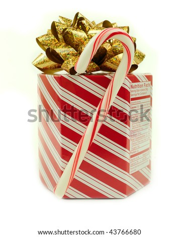Box of christmas candies with a candy cane isolated over white