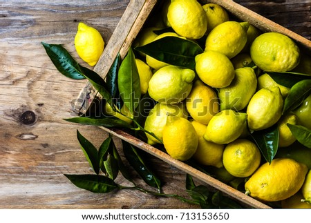 box of fresh lemons with lemon tree leaves