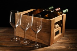 Box with bottles of wine and empty glasses on wooden table