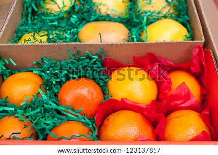 Box with citrus fruits - oranges, grapefruits and tangerines packed  carefully to be sent out as a gift. selective focus